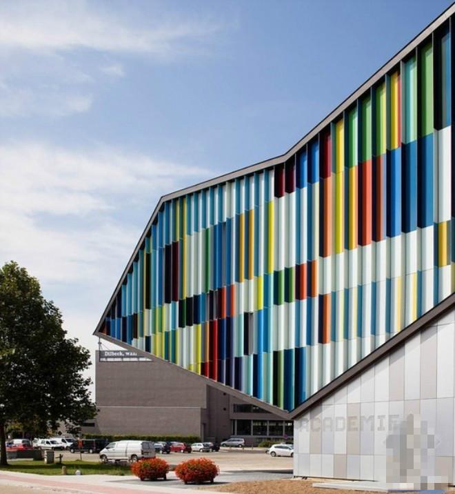 这所比利时的艺术学校外墙,就像一面大的彩虹墙一样,在周围绿树